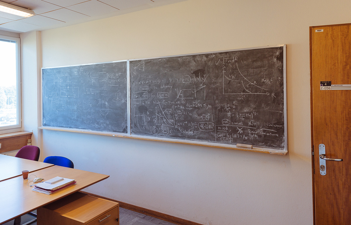 "Asimina Arvanitaki's desk on CERN campus.The blackboards contain formulae that Asimina explains ""the one on the left (close to the window) is a possible design for a dark matter detector, while the one on the right is a new theory that explains the mass of the higgs, the so called hierarchy problem.  Another way to understand the latter is that it is equivalent to the question why is gravity so weak? You can see that gravity is many orders of magnitude weaker than anything else, since everytime you lift for example a cup, the forces in your arm overcome the gravitational pull of an entire planet…"""