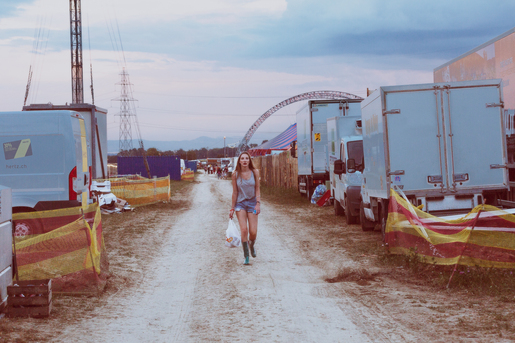 Paléo festival 2016. A girl walks on the dustroad behind the foodstands.